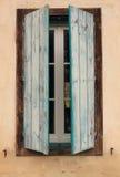 Chiuda su della metà dei vecchi otturatori blu rustici aperti della finestra su una facciata beige di vecchia casa dell'azienda a Fotografie Stock Libere da Diritti