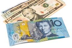 Chiuda su della nota di valuta del dollaro australiano contro il dollaro americano Fotografia Stock