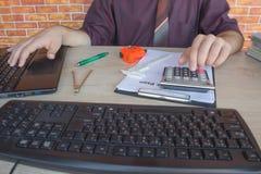 Chiuda su della penna di tenuta della mano dell'uomo d'affari che lavora al calcolatore, al documento della contabilità ed al com Fotografia Stock