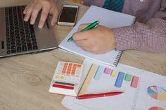 Chiuda su della penna di tenuta della mano dell'uomo d'affari che lavora al calcolatore, al documento della contabilità ed al com Fotografie Stock