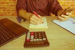 Chiuda su della penna di tenuta della mano dell'uomo d'affari che lavora al calcolatore, al documento della contabilità ed al com Immagini Stock Libere da Diritti