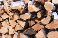 Chiuda su della pila di legno innevata fotografia stock libera da diritti