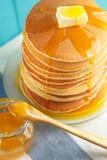 Chiuda su della pila di pancake con miele e burro Fotografia Stock Libera da Diritti