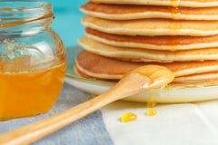 Chiuda su della pila di pancake con miele di versamento, il cucchiaio di legno ed il barattolo di miele Fotografia Stock Libera da Diritti