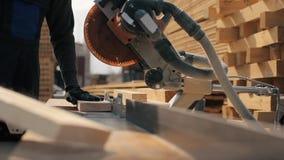 Chiuda su della plancia di legno dei tagli della tagliatrice Il lavoratore taglia i bordi di legno archivi video