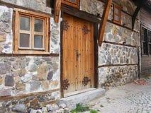 Chiuda su della porta antica della vecchia casa di pietra con i montaggi del metallo Fotografia Stock Libera da Diritti