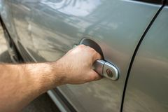 Chiuda su della porta di automobile maschio umana di apertura della mano Fotografie Stock
