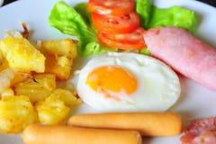 Chiuda su della prima colazione con l'uovo fritto, la salsiccia, il prosciutto e la patata immagine stock libera da diritti