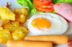 Chiuda su della prima colazione con l'uovo fritto, la salsiccia, il prosciutto e la patata fotografia stock