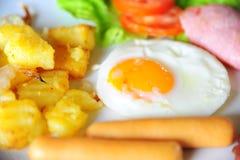 Chiuda su della prima colazione con l'uovo fritto, la salsiccia, il prosciutto e la patata fotografia stock libera da diritti