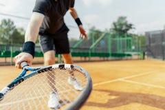 Chiuda su della racchetta della tenuta dell'uomo alla mano destra ed alla battitura una pallina da tennis immagine stock libera da diritti