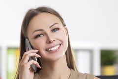 Chiuda su della ragazza allegra nel beige sul telefono Fotografie Stock