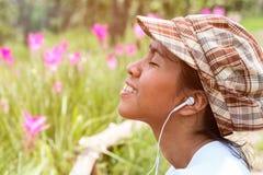 Chiuda su della ragazza asiatica che ascolta la musica da Internet mobile con sorridere Immagine Stock