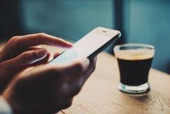 Chiuda su della ragazza che per mezzo dello smartphone e prenda un coffe Fotografie Stock Libere da Diritti