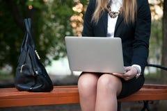 Chiuda su della ragazza che si siede con il computer portatile Immagine Stock Libera da Diritti