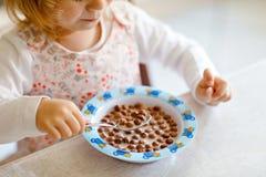 Chiuda su della ragazza del bambino che mangia il cereale sano con latte per il bambino felice sveglio del bambino della prima co fotografie stock libere da diritti