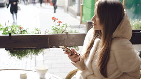 Chiuda su della ragazza graziosa che utilizza il telefono nel caffè quando il caffè sta cocendo a vapore 4K stock footage