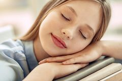 Chiuda su della ragazza minuta che dorme sui libri Immagini Stock Libere da Diritti