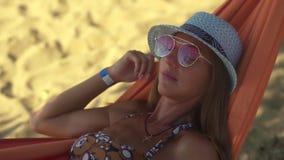Chiuda su della ragazza nell'amaca sulla spiaggia stock footage