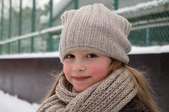 Chiuda su della ragazza sveglia sorridente con il cappello tricottato l'inverno Colpo all'aperto con fondo vago unfocused immagini stock