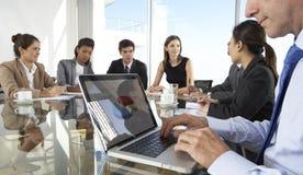 Chiuda su della riunione di consiglio di Using Laptop During dell'uomo d'affari intorno immagini stock
