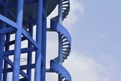 Chiuda su della scala a chiocciola blu sul serbatoio di acqua Elevated Fotografia Stock