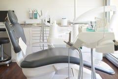 Chiuda su della sedia e dell'attrezzatura vuote ad una chirurgia dentale fotografie stock