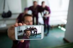 Chiuda su della squadra di baseball che clicca il selfie mentre stanno allo spogliatoio Fotografia Stock