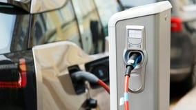 Chiuda su della stazione di carico Un cavo è collegato alla stazione, che fa pagare un'automobile elettrica archivi video