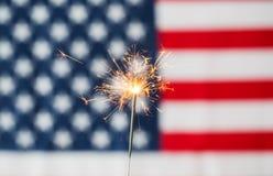 Chiuda su della stella filante che brucia sopra la bandiera americana Fotografia Stock
