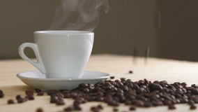 Chiuda su della tazza bianca di caffè d'evaporazione sui semi di cacao torrefatti vicino della tavola lentamente video d archivio
