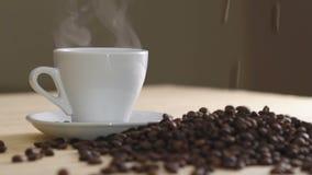 Chiuda su della tazza bianca di caffè d'evaporazione sui semi di cacao torrefatti vicino della tavola lentamente archivi video