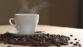 Chiuda su della tazza bianca di caffè d'evaporazione sui semi di cacao torrefatti vicino della tavola lentamente stock footage