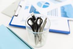 Chiuda su della tazza con le forbici e le penne all'ufficio Immagini Stock