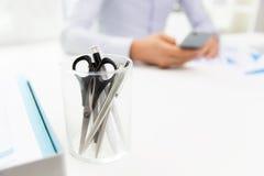 Chiuda su della tazza con le forbici e le penne all'ufficio Fotografia Stock Libera da Diritti