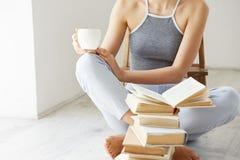Chiuda su della tazza di caffè del libro della tenuta della ragazza che si siede sul pavimento con i libri sopra la parete bianca Fotografia Stock Libera da Diritti