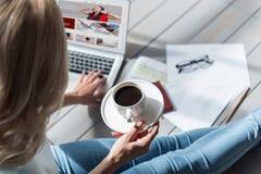 Chiuda su della tazza di caffè della tenuta della donna e computer portatile usando Fotografie Stock