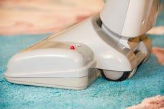 Chiuda su della testa di un aspirapolvere moderno che è usando mentre aspirazione un tappeto spesso di bianco del mucchio Fotografie Stock