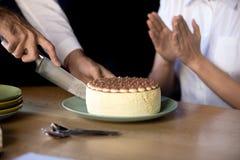 Chiuda su della torta di compleanno di taglio dell'uomo in ufficio fotografia stock libera da diritti