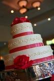 Chiuda su della torta nunziale con rosso ribben Fotografia Stock Libera da Diritti