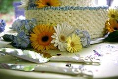 Chiuda su della torta nunziale e del coltello gialli Fotografia Stock Libera da Diritti