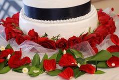 Chiuda su della torta nunziale e delle rose Immagine Stock