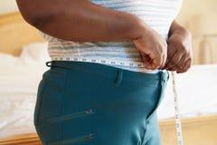 Chiuda su della vita di misurazione della donna di peso eccessivo Immagine Stock