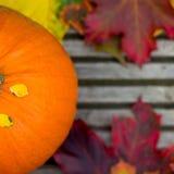 Chiuda su della zucca e di Autumn Leaves arancio su Backg di legno Fotografie Stock Libere da Diritti