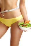 Chiuda su delle anche di misurazione di una donna con un'insalata in sua mano Immagini Stock
