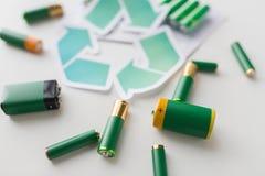 Chiuda su delle batterie e del simbolo di riciclaggio verde Immagine Stock Libera da Diritti