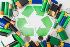 Chiuda su delle batterie e del simbolo di riciclaggio verde Fotografia Stock