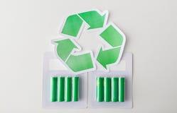 Chiuda su delle batterie e del simbolo di riciclaggio verde Immagine Stock