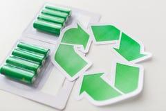 Chiuda su delle batterie e del simbolo di riciclaggio verde Immagini Stock