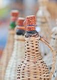 Chiuda su delle bottiglie della damigiana con la spina della pannocchia di granturco al mercato del ricordo in Romania Fotografia Stock